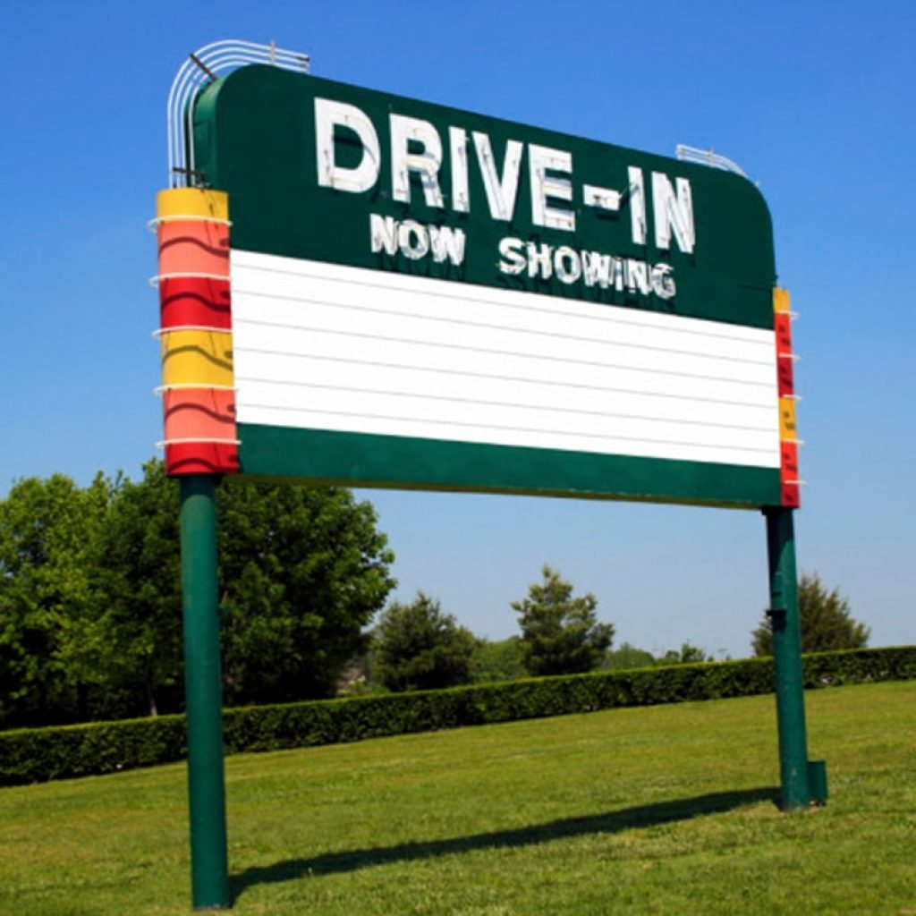 drive-in sign on a grassy lawn with trees and a blue sky in the background